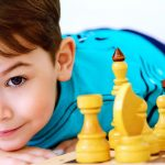 Considering Chess Tactics a Little Boy Leaning Over Chess Set