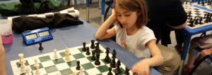 Girl at chess board with digital chess clock.