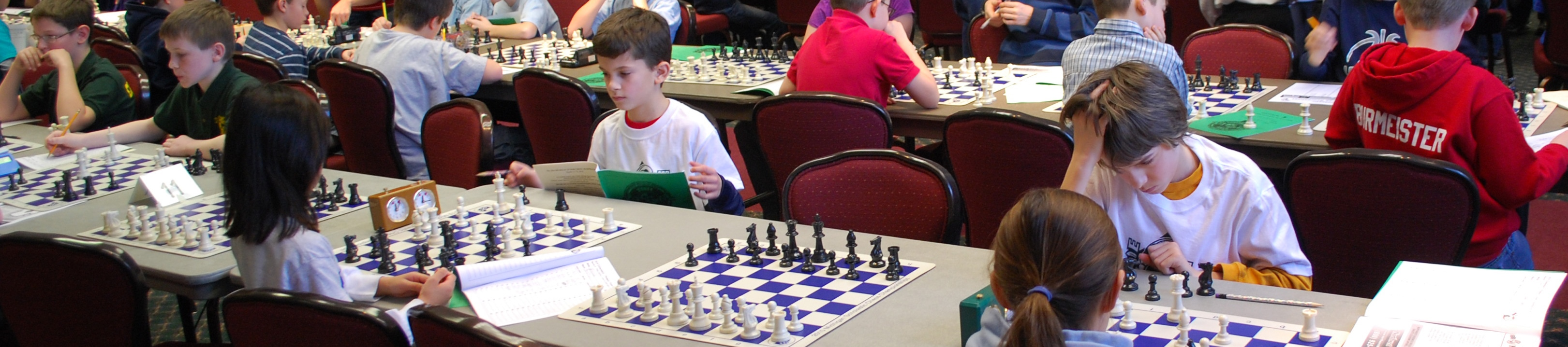 Kids playing in chess tournament.
