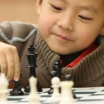 Asian boy makes chess move
