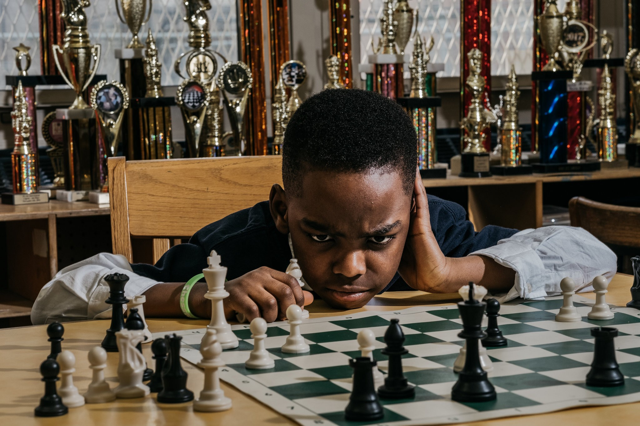 Tani Adewumi chin on table looking at chess position
